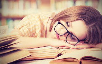 tired student girl with glasses sleeping on the books in the library ** Note: Shallow depth of field