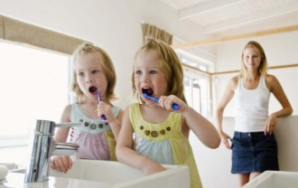 Mother and twin girls brushing teeth